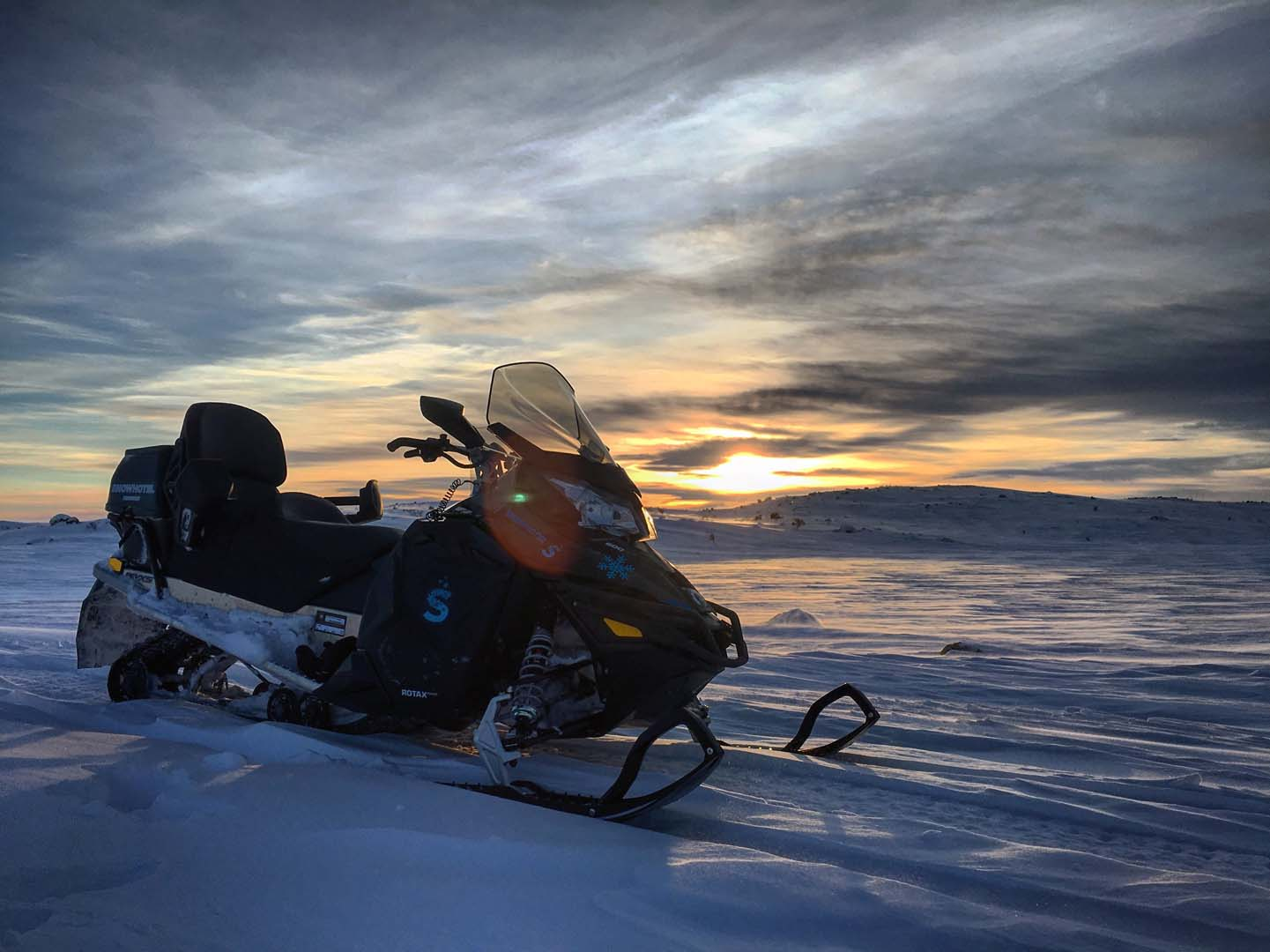 Snowmobiling into an arctic sunset in Norway