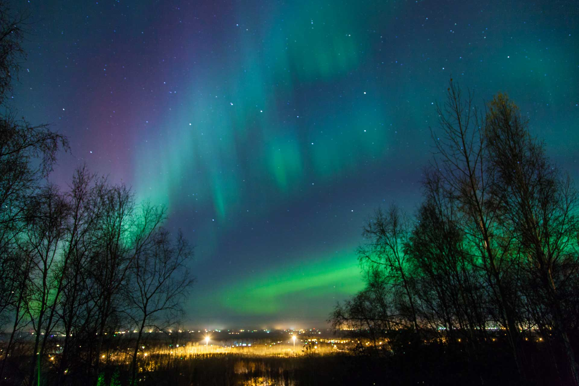 Northern lights and city lights in Scandinavia