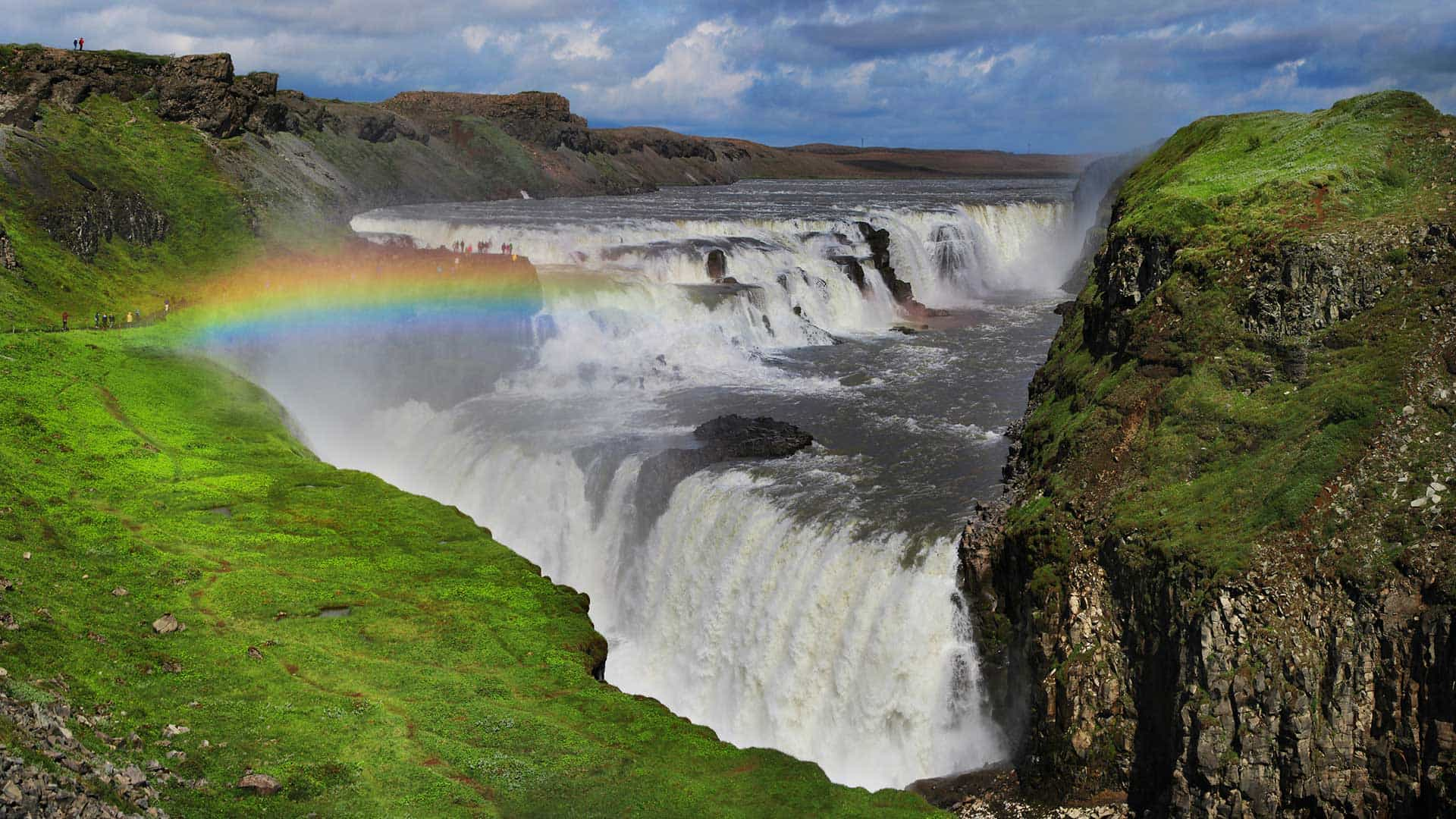 A rainbow glows in the mist at Gullfoss waterfall in Iceland