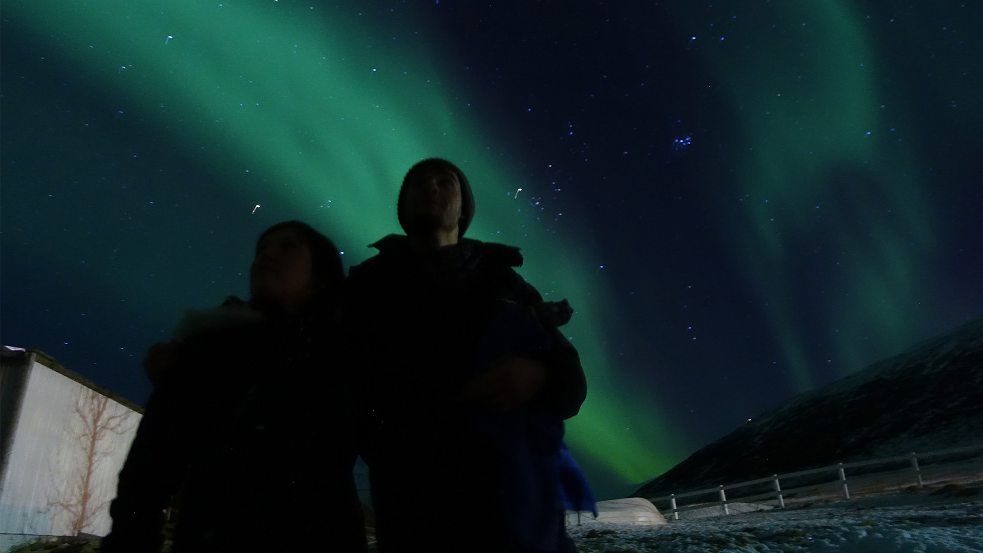 couple standing under northern lights