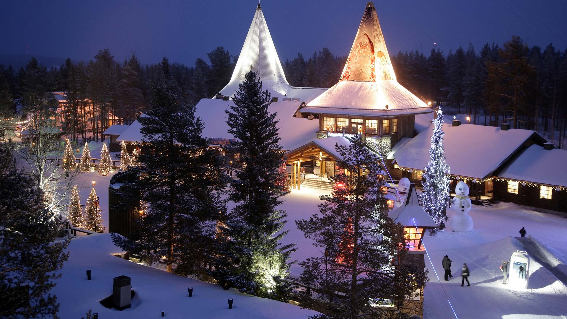 Snow covered building and Christmas trees in Santa Claus Village