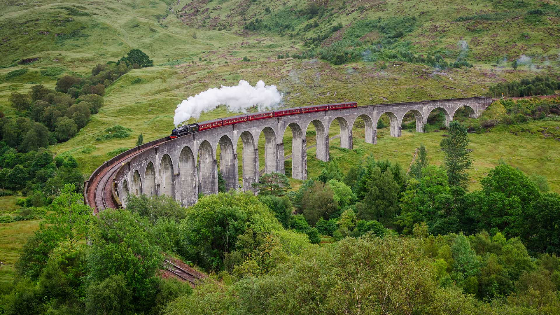 jacobite steam train going over glenfinnan viaduct
